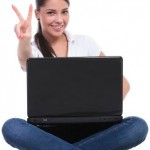 casual woman sits with laptop & victory