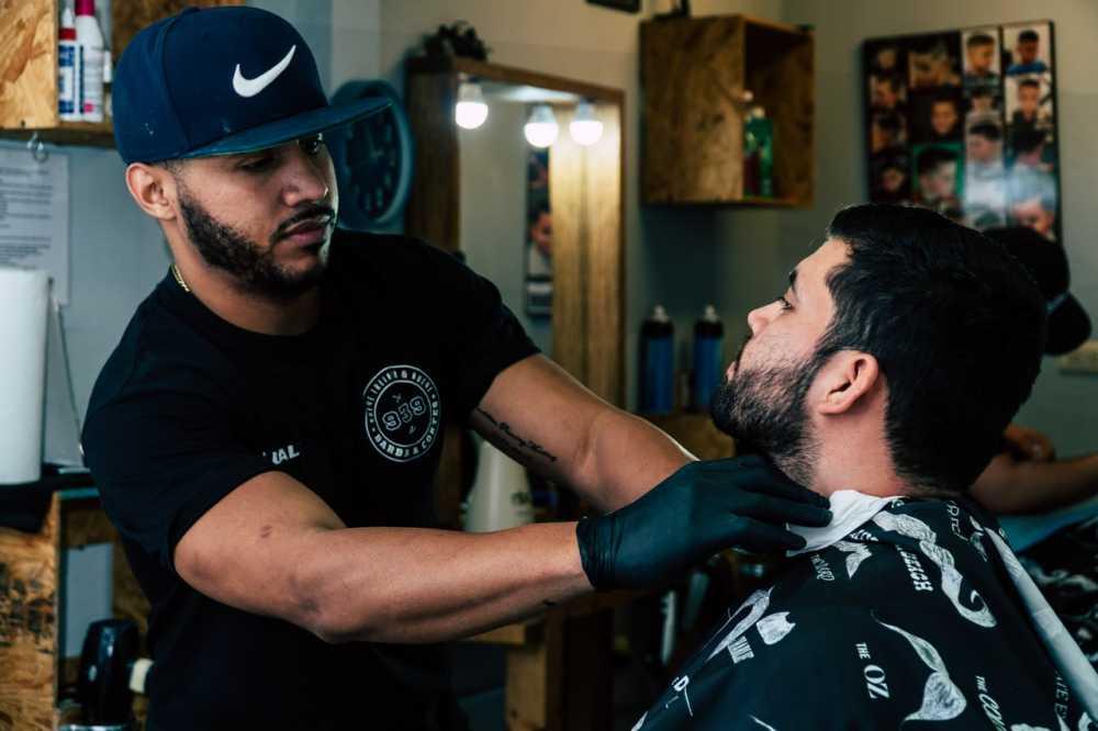Entrepreneur barber shaving costumer